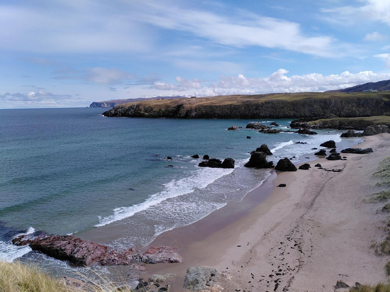 Looking down to a sandy beach which is peppered in its North corner by small stacks. The water is calm and stretches out to the left. Light, long clouds fill the sky and the top of the bay is met with a smal cliff-face.