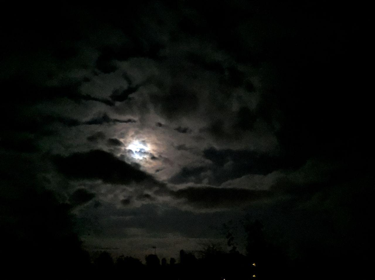 Night sky with some clouds in front of a bright moon