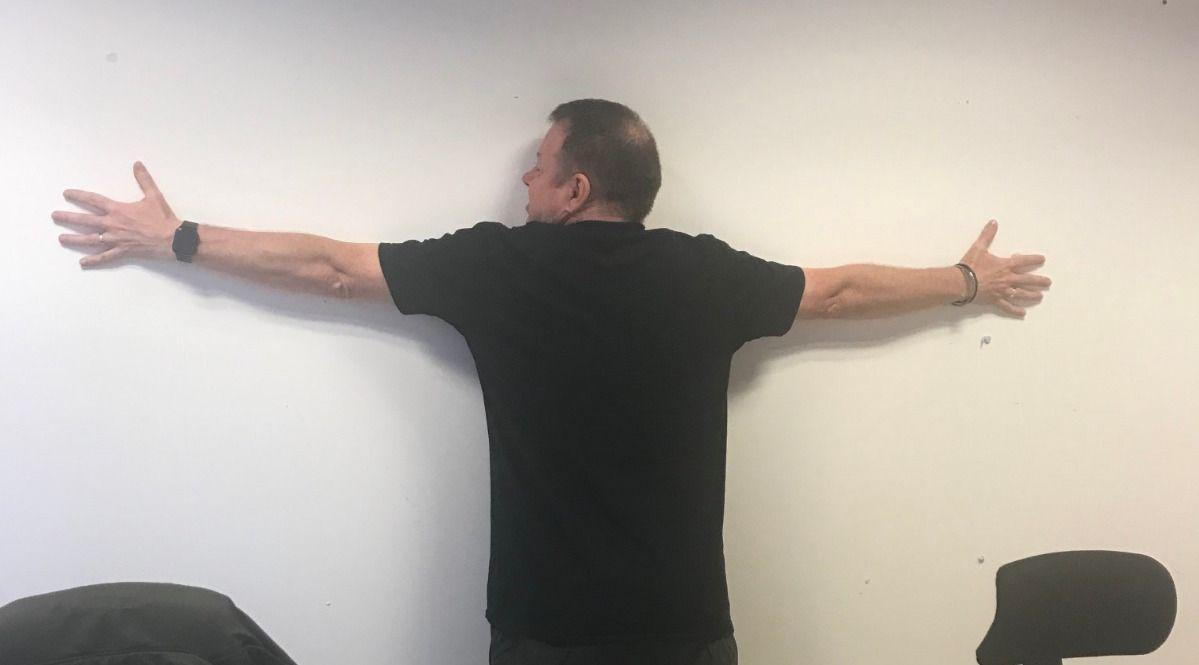 Graham Thompson back to camera, arms out-stretched against whiteboard in the office.