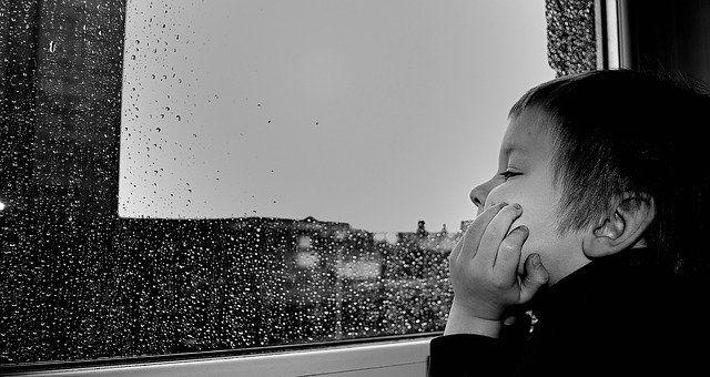 A young boy, staring out a window on a rainy day