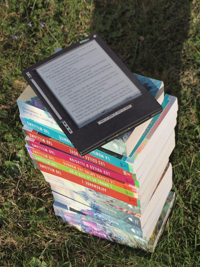 An ebook reader atop a stack of printed books