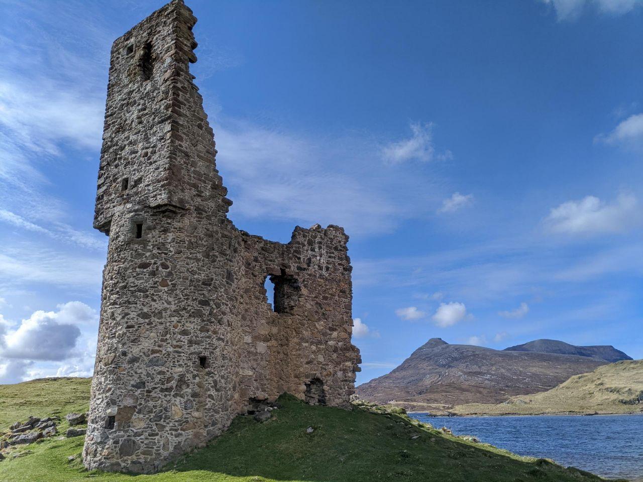 Stone wall fills the foreground, rounded bottom and a flattened face on the higher half. Ruined wall on the right side falls away steeply. Clear, cold, skies above. A few rounded Bens in the background.