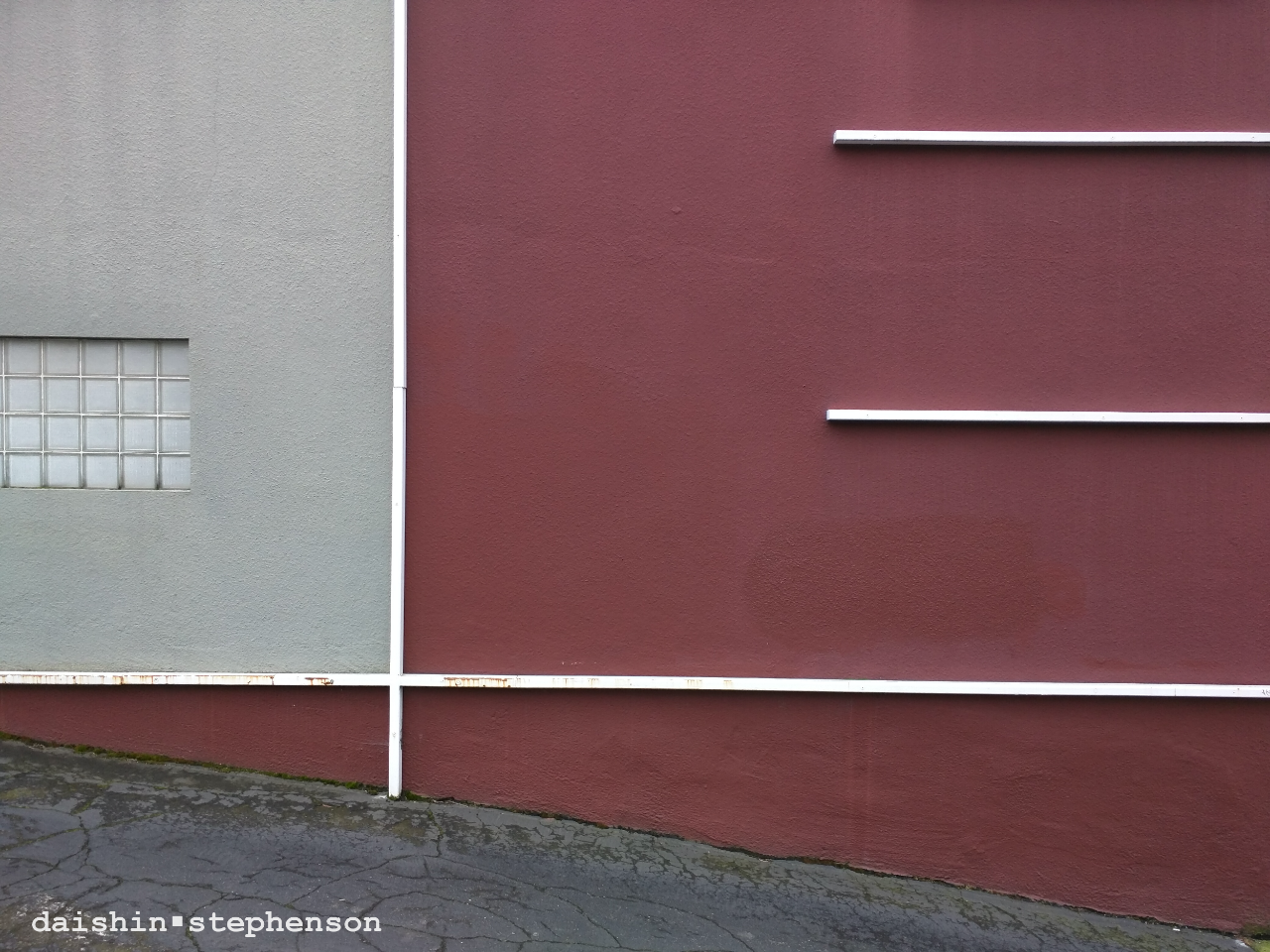 red exterior building wall with orthogonal piping