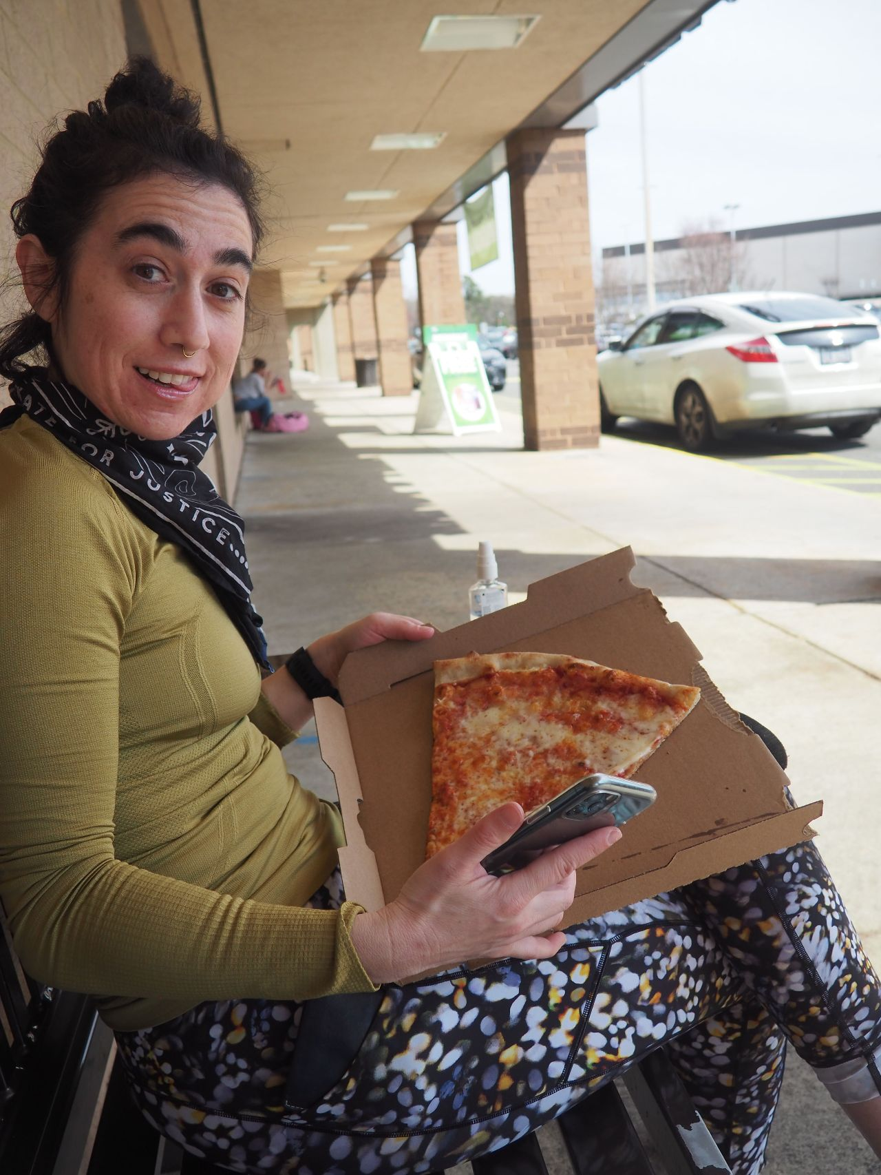 A woman with dark curly hair holding a slice of pizza.