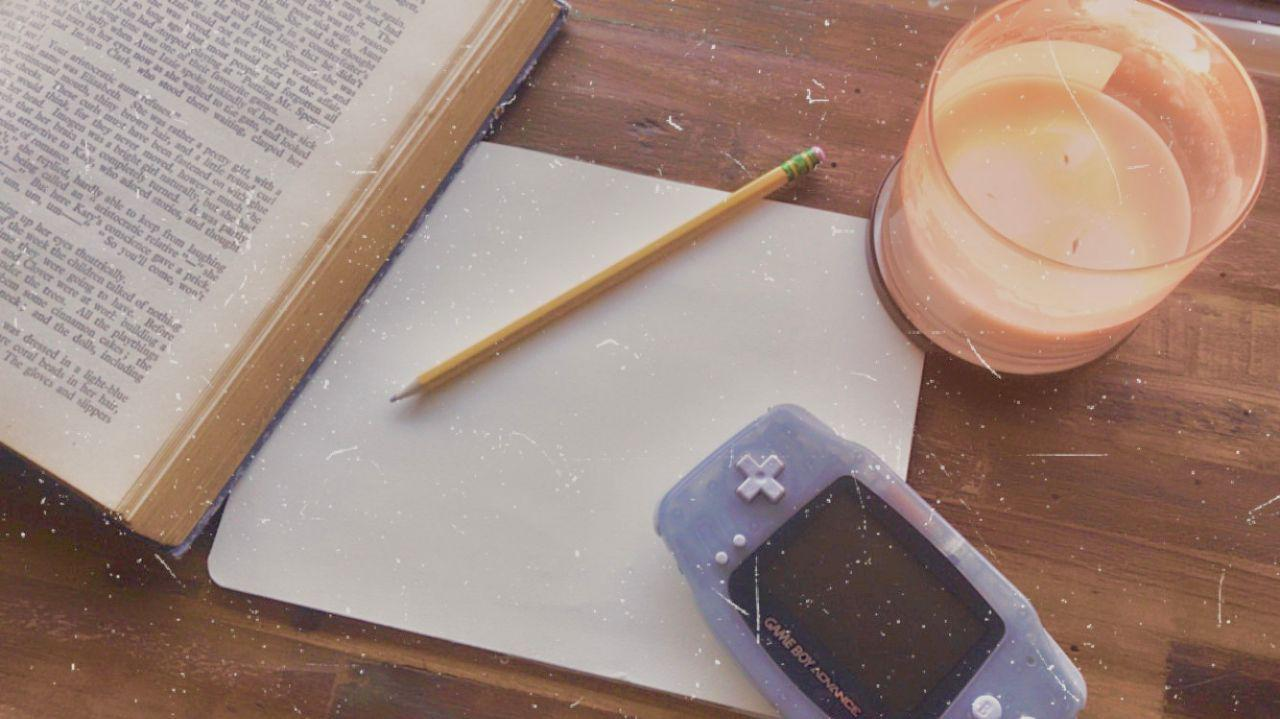 A sheet of paper, a pencil, a book and a GameBoy sprawled on a wooden surface.