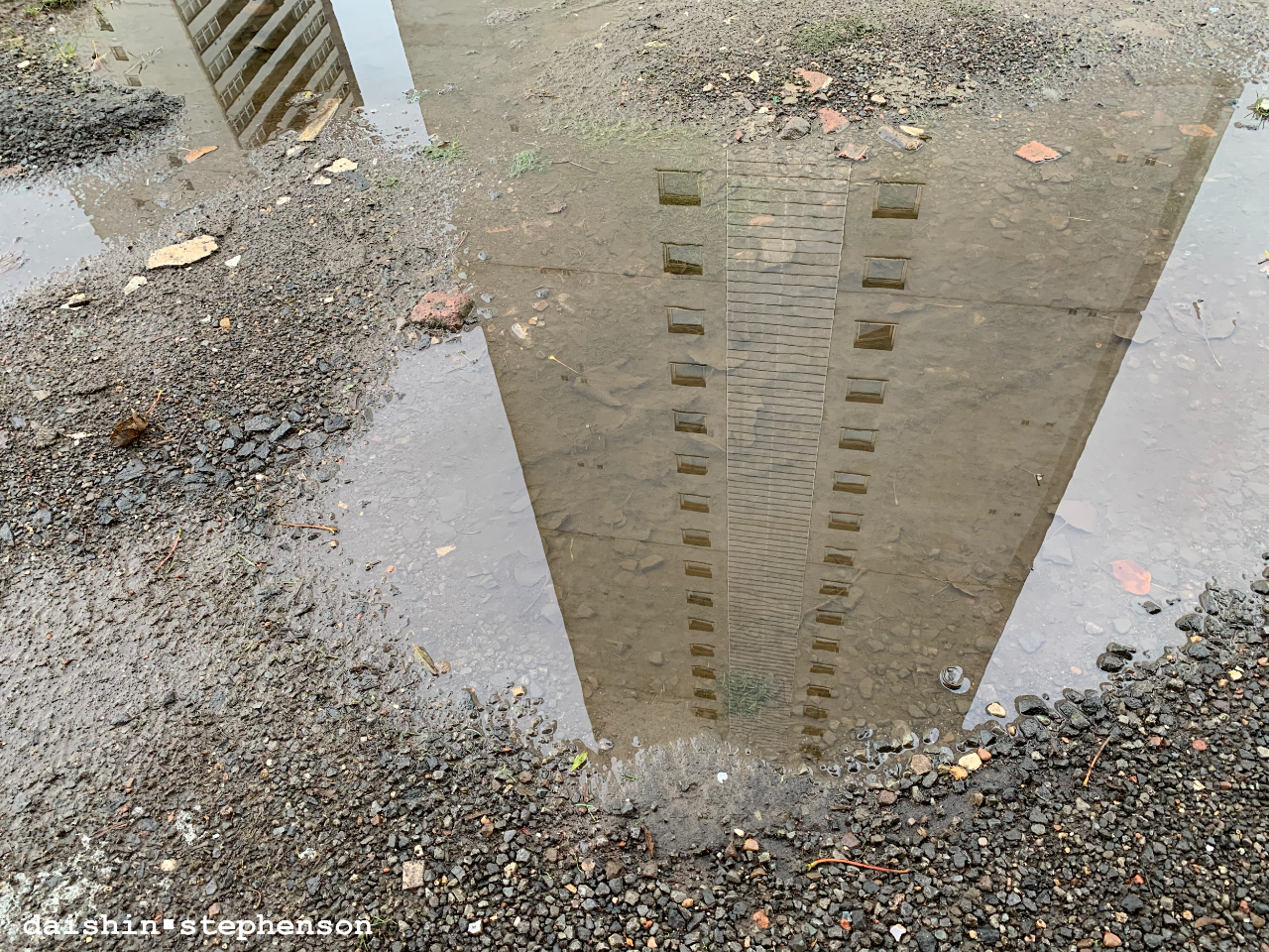 reflection of high flat in puddle