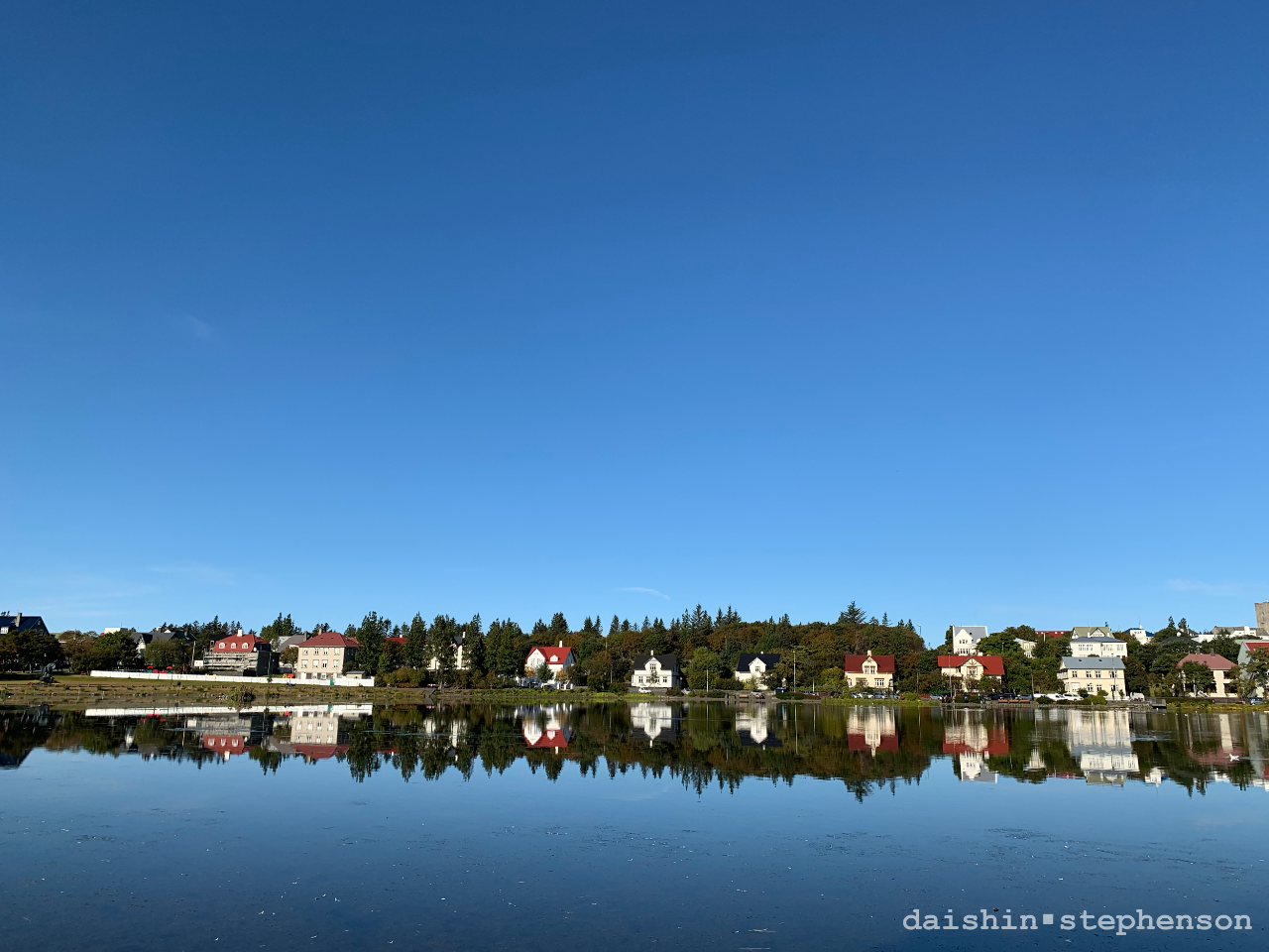 reykjavik city reflected in lake