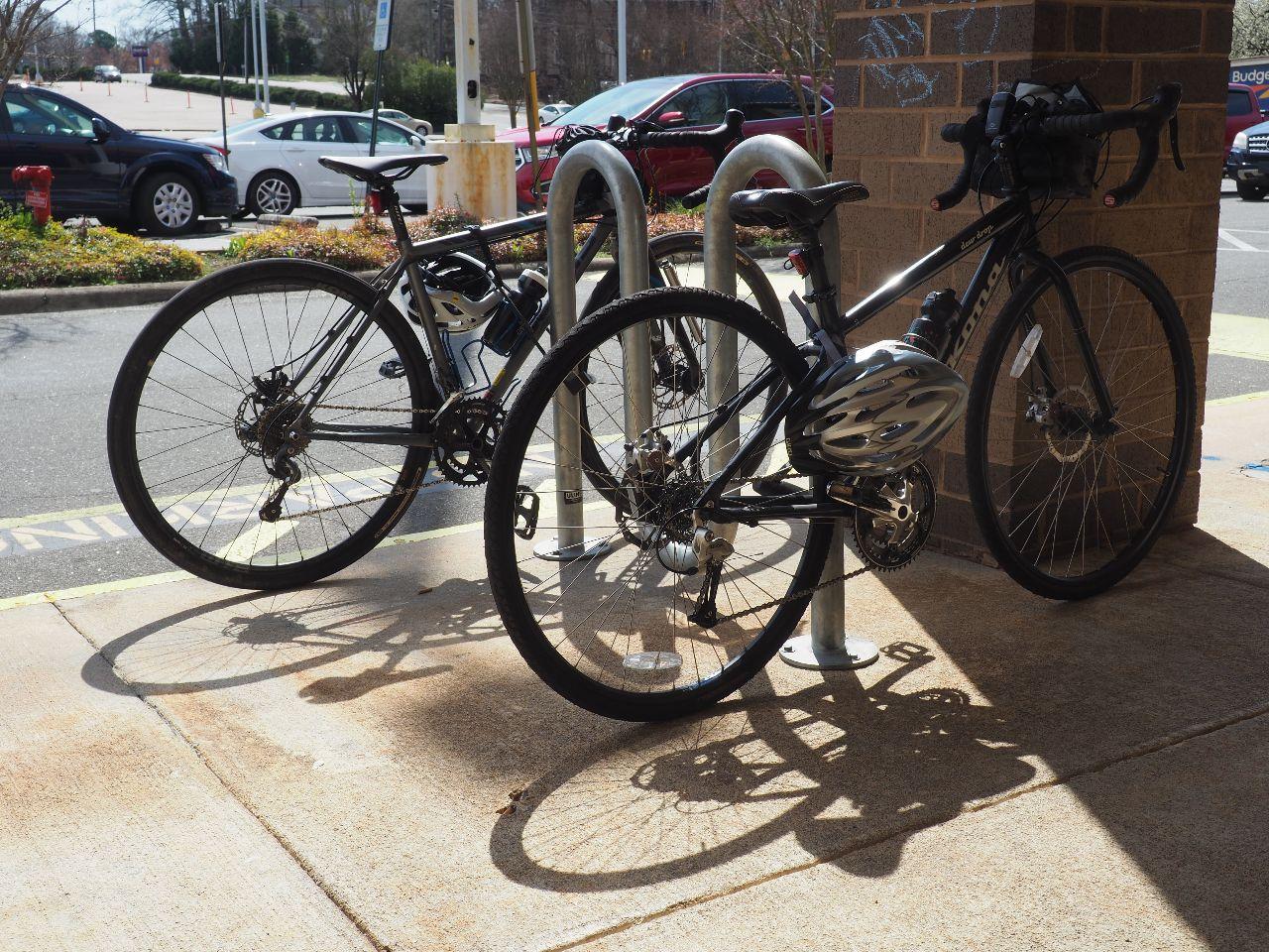 Two bikes at a bike rack.