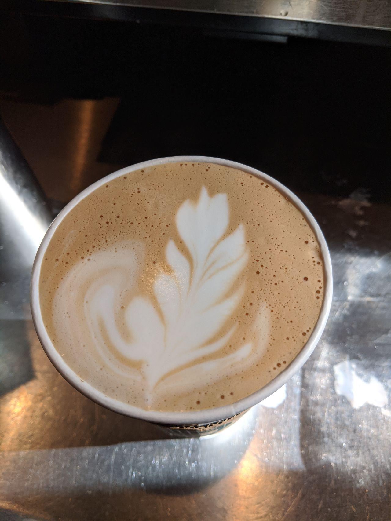 The top of a Flat White, with a white flower/leaf in the foam.