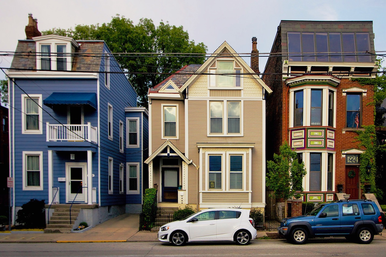 Street shot of 3 homes that are colored blue, white, and red alternatively