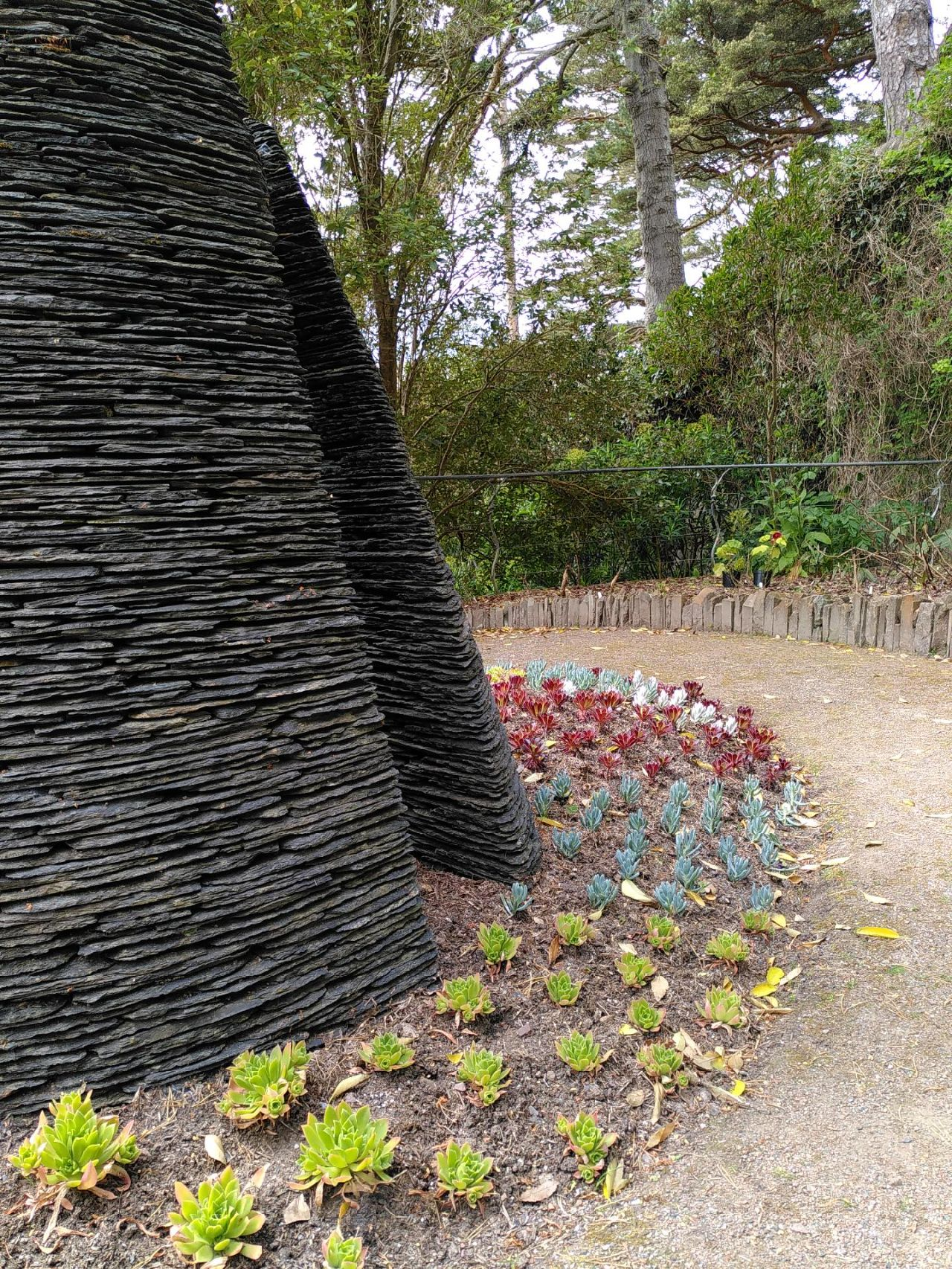 Tall conical slate structure on the left with succulent plants spaced regularly around the base. Their colour changes from bright green to dull green/blue to deep red. A gravel path leads from bottom right to middle. Background is greenery.