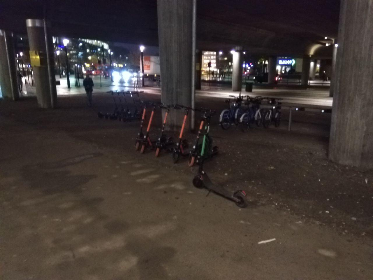 E-scooters standing in line under a bridge trying to become a big trend this year. It is dark enda