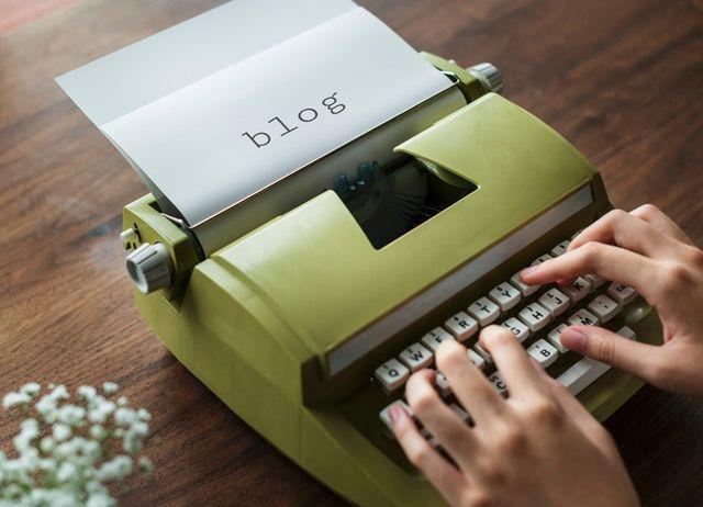 The word 'BLOG' typed on a small green manual typewriter