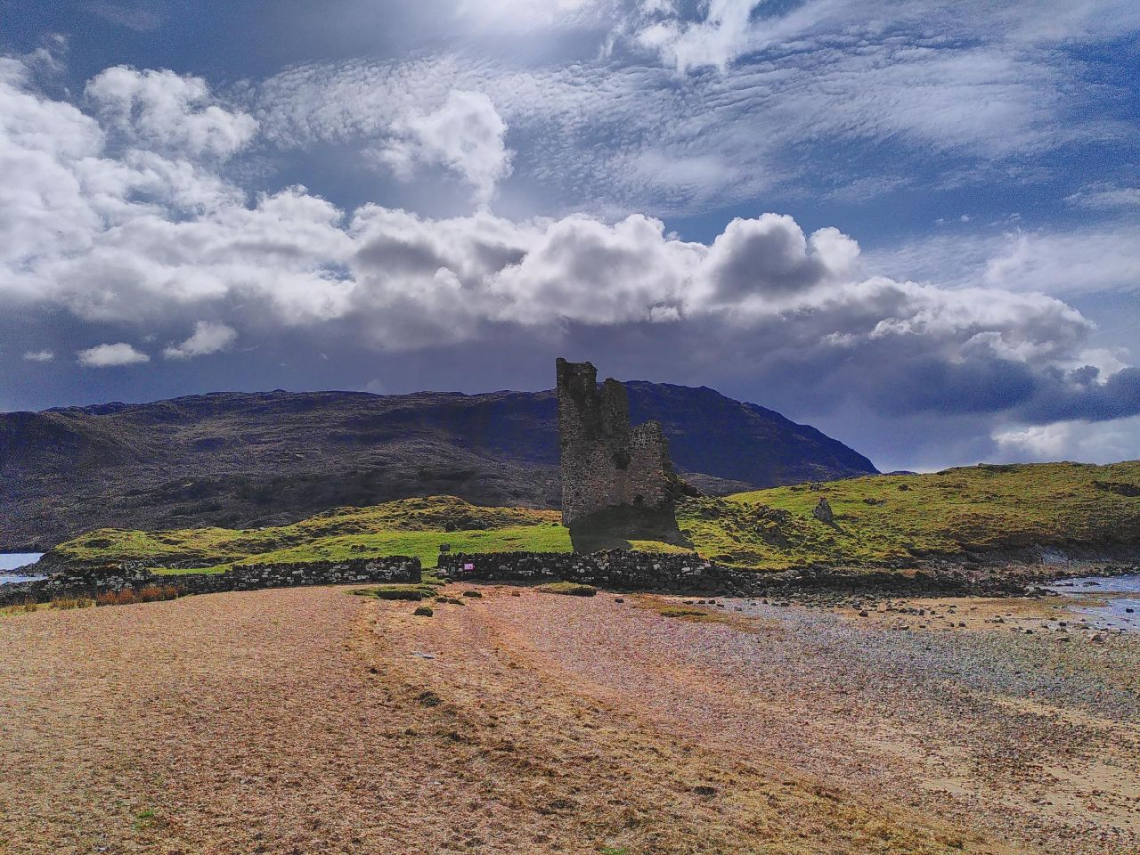 Foreground of shingle leading to a small stone-wall that holds green rocky land. The castle sits in the middle, torn almost in half, the wal on the right standing. Reasonably clear skies light the picture.