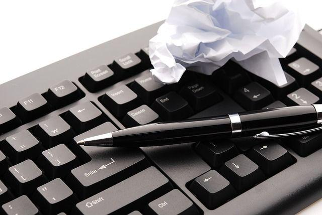 A keyboard, a pen, and some crumpled paper