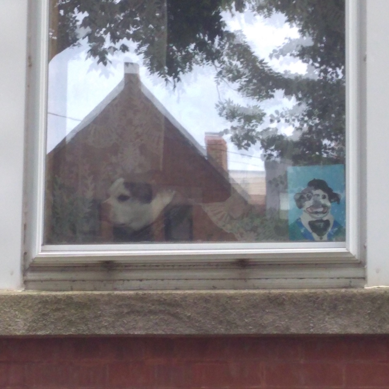 A dog in a window, sitting next to a small painting of himself