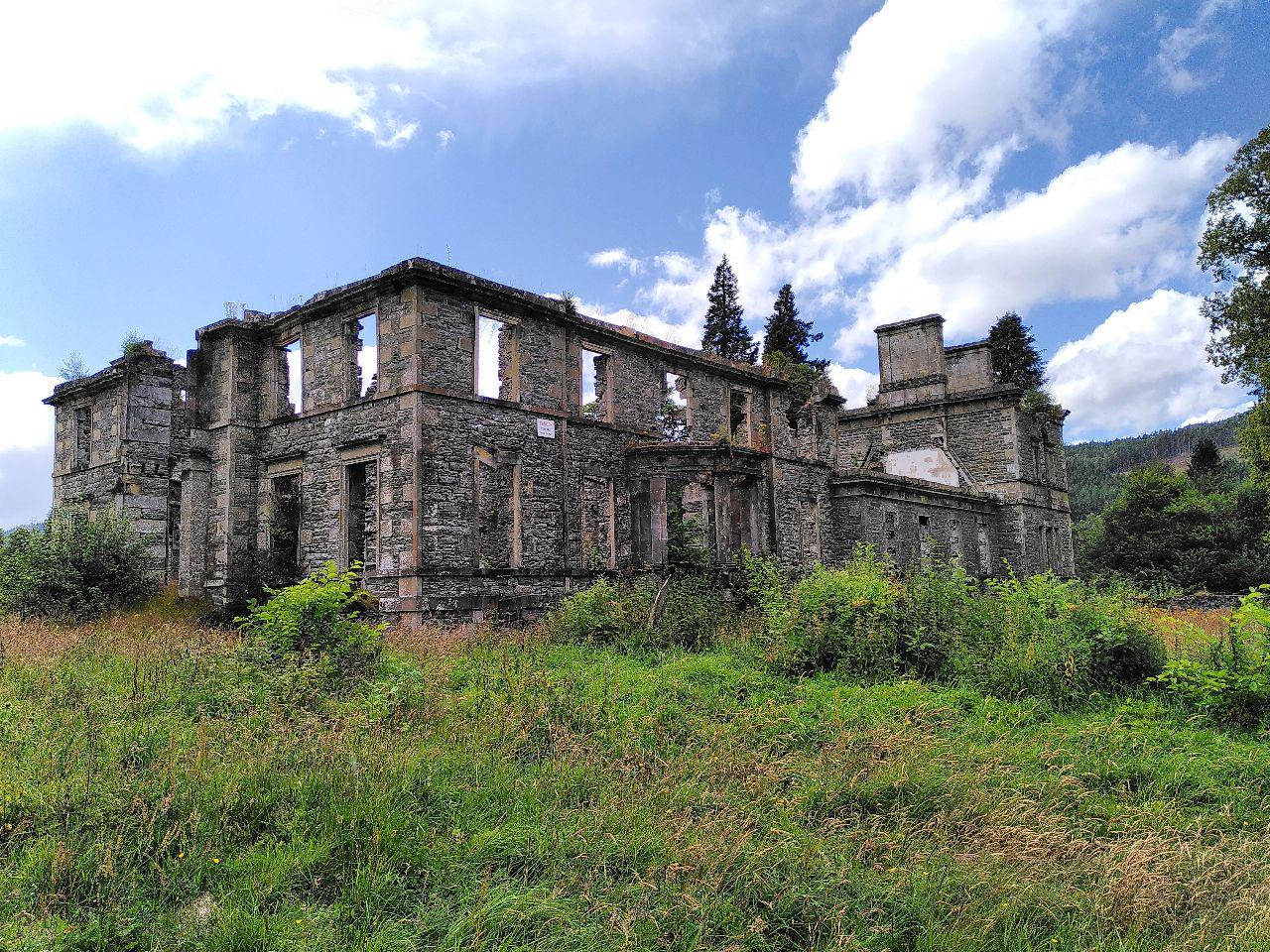 Large, 3 story, mansion that is derelict. No roof and bare stone. Grass is overgrowing in the foreground. Clear skies above.
