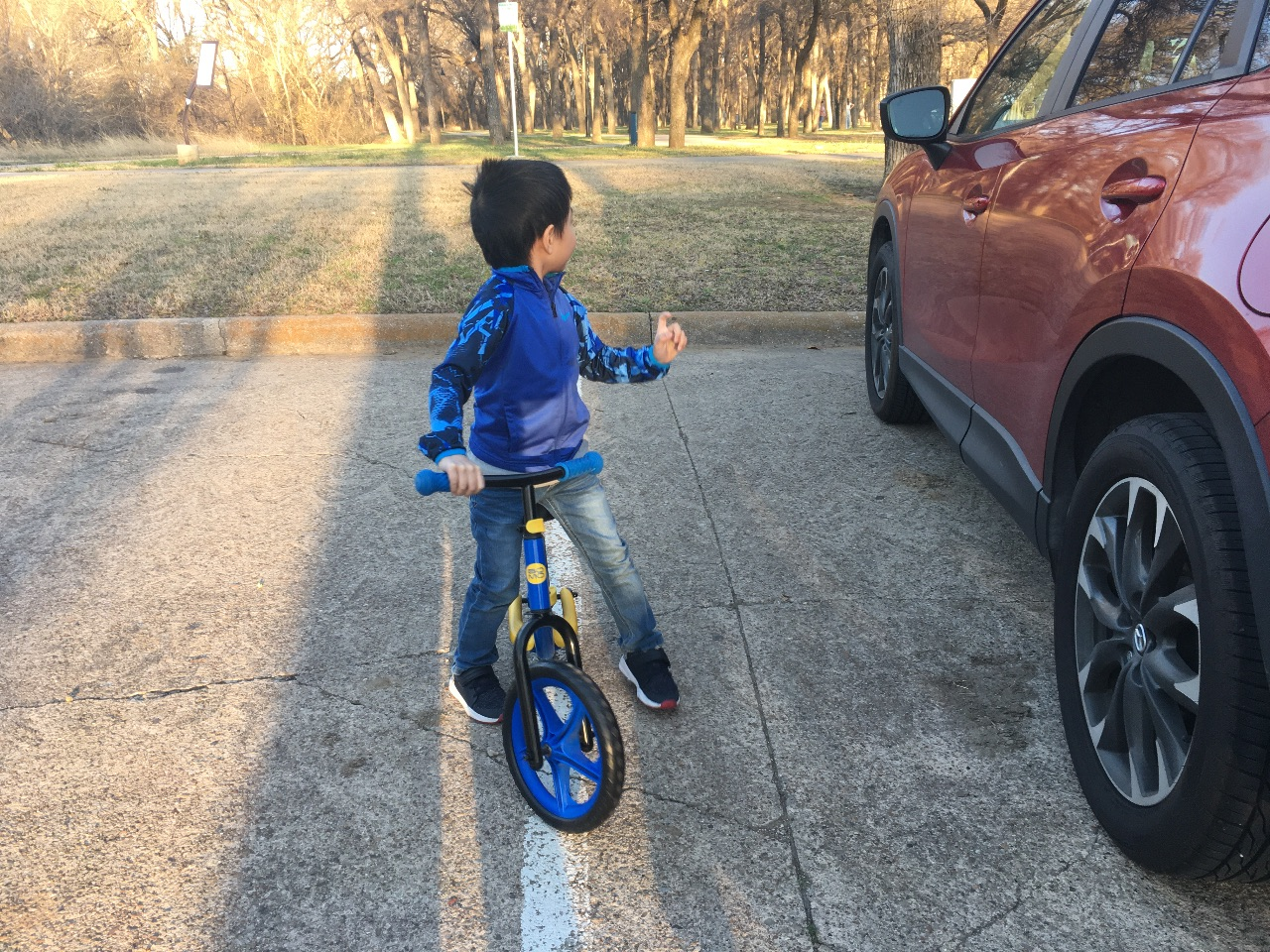 Davin excited to ride his balance bike at the park.