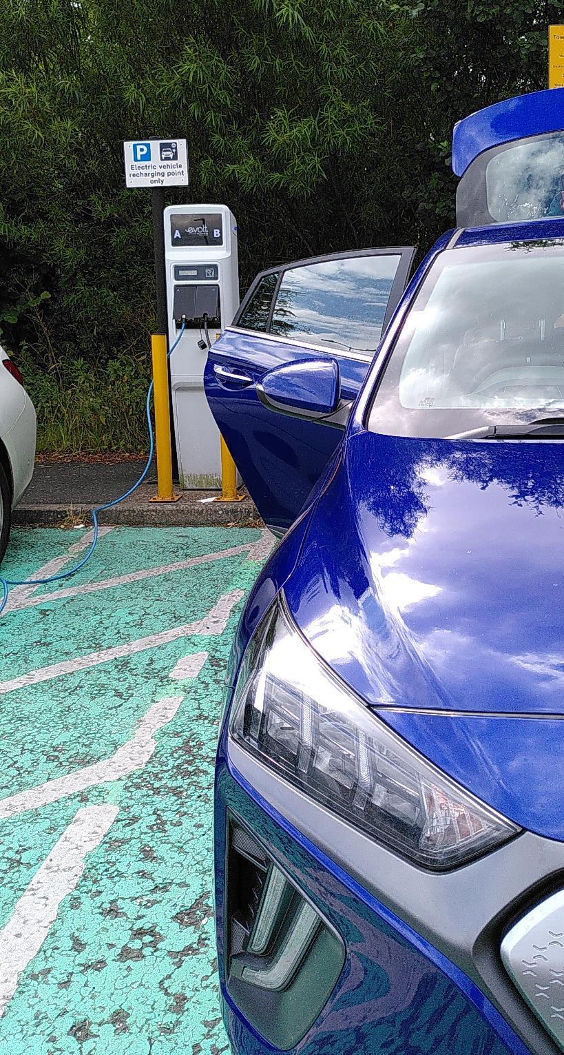 Blue car with door and boot open plugged into a white charging station