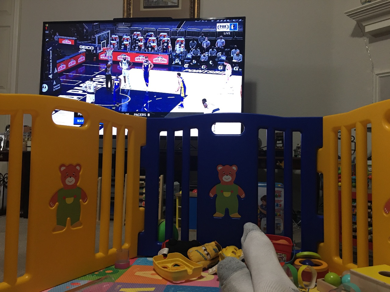 Watching a basketball game from inside the play pen.