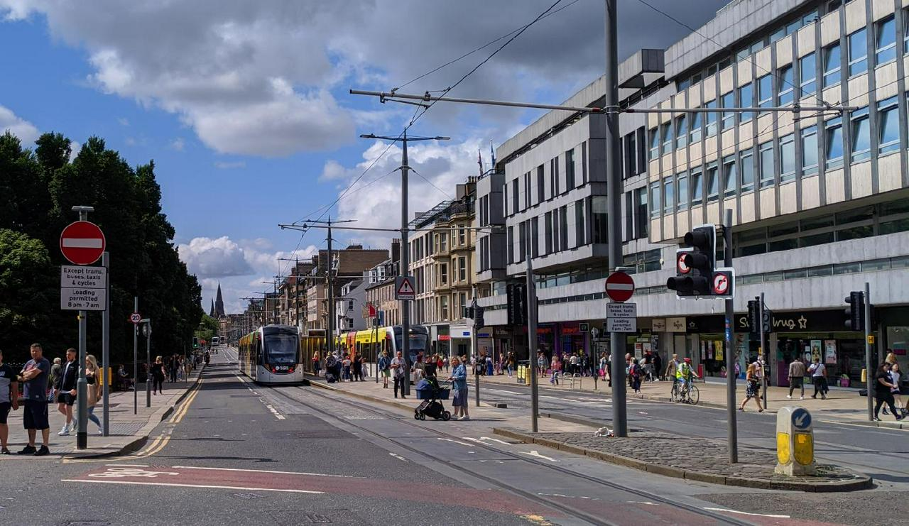 A picture of Princes Street, Edinburgh. There're two trams at the tram station. The street is busy with people walking around but little on the road.