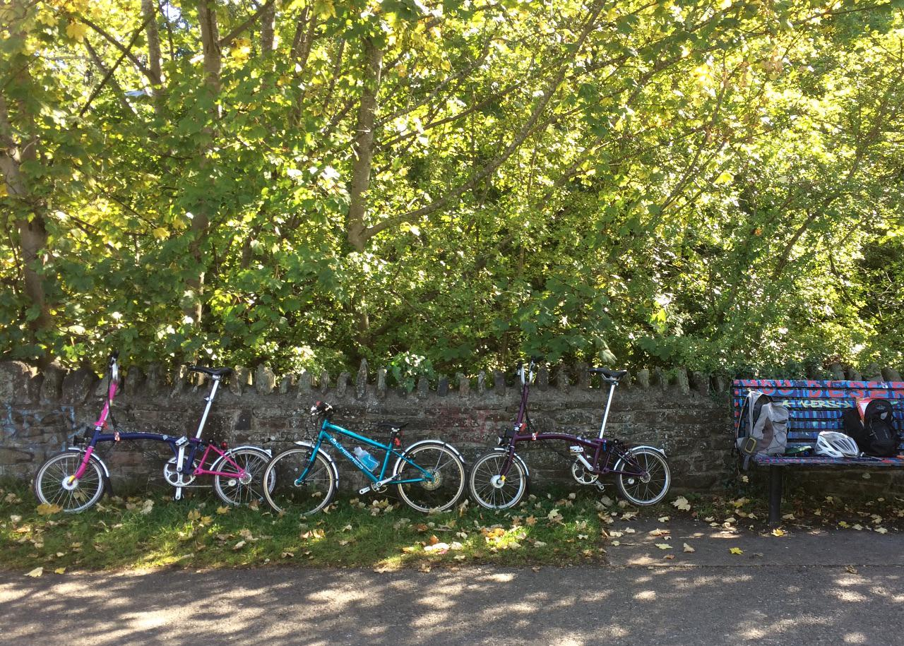 Two Brompton bikes and a child's Islabike lean against a wall on the Bristol-Bath cycle path