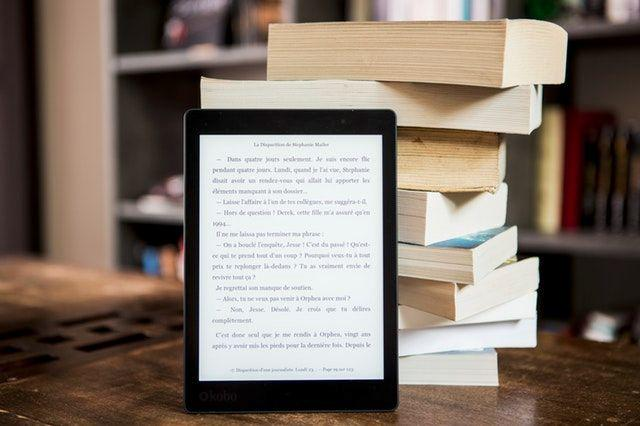 An ebook reader in front of a stack of books