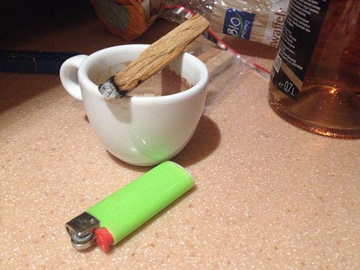 empty espresso cup, previously lit wood stick on top, lighter next to it