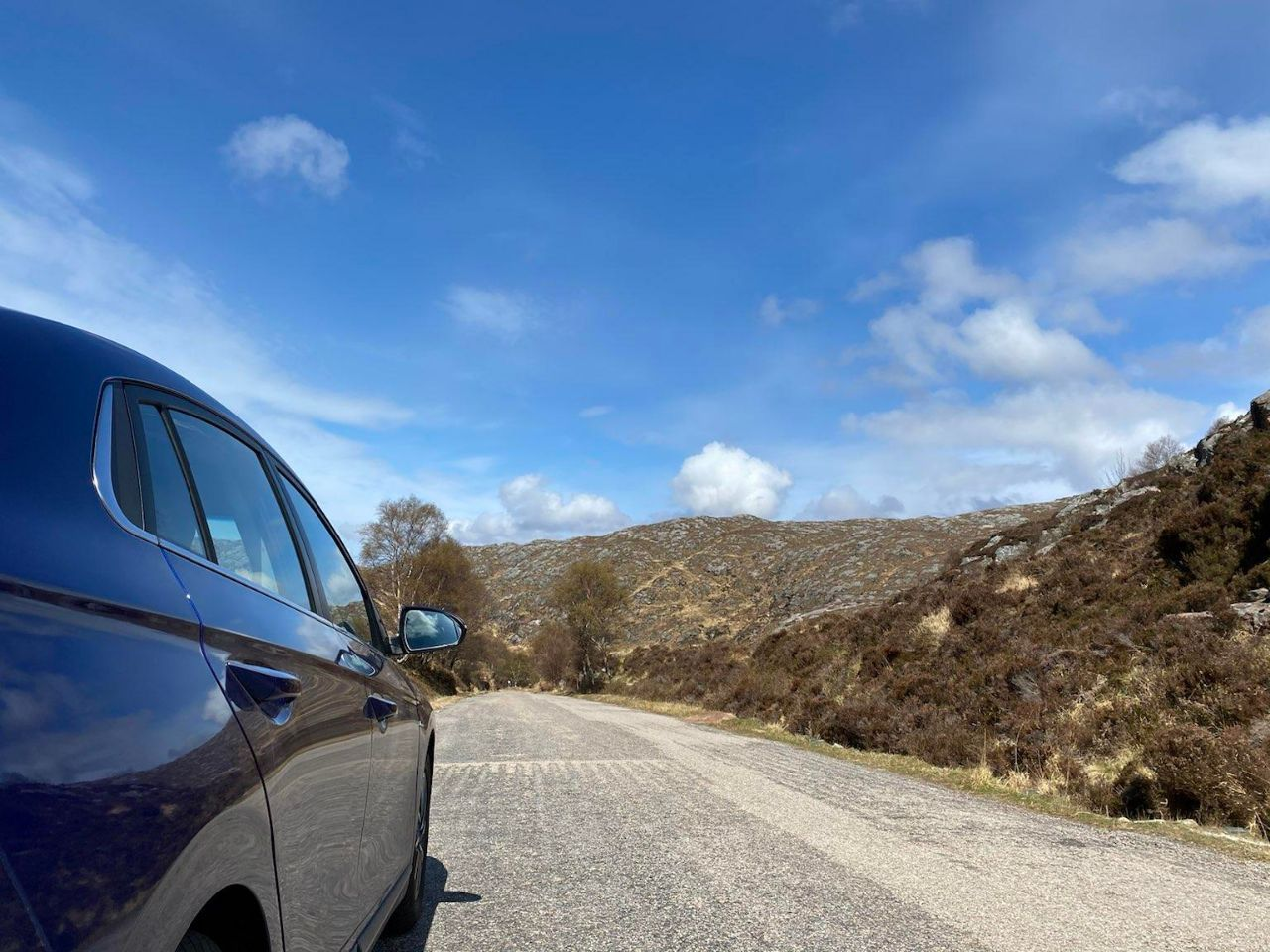 Blue car sat the side of an empty single carriage-road. Open skies light up a heather-covered hill