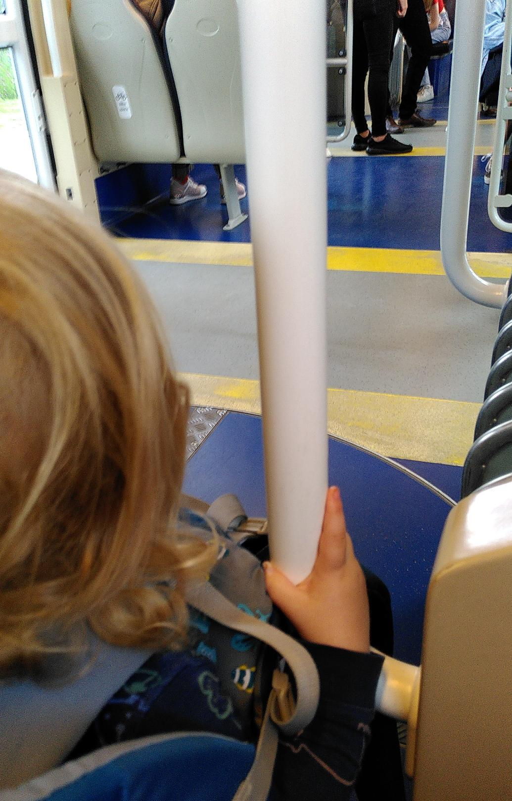 Small Child holding the rail inside the tram