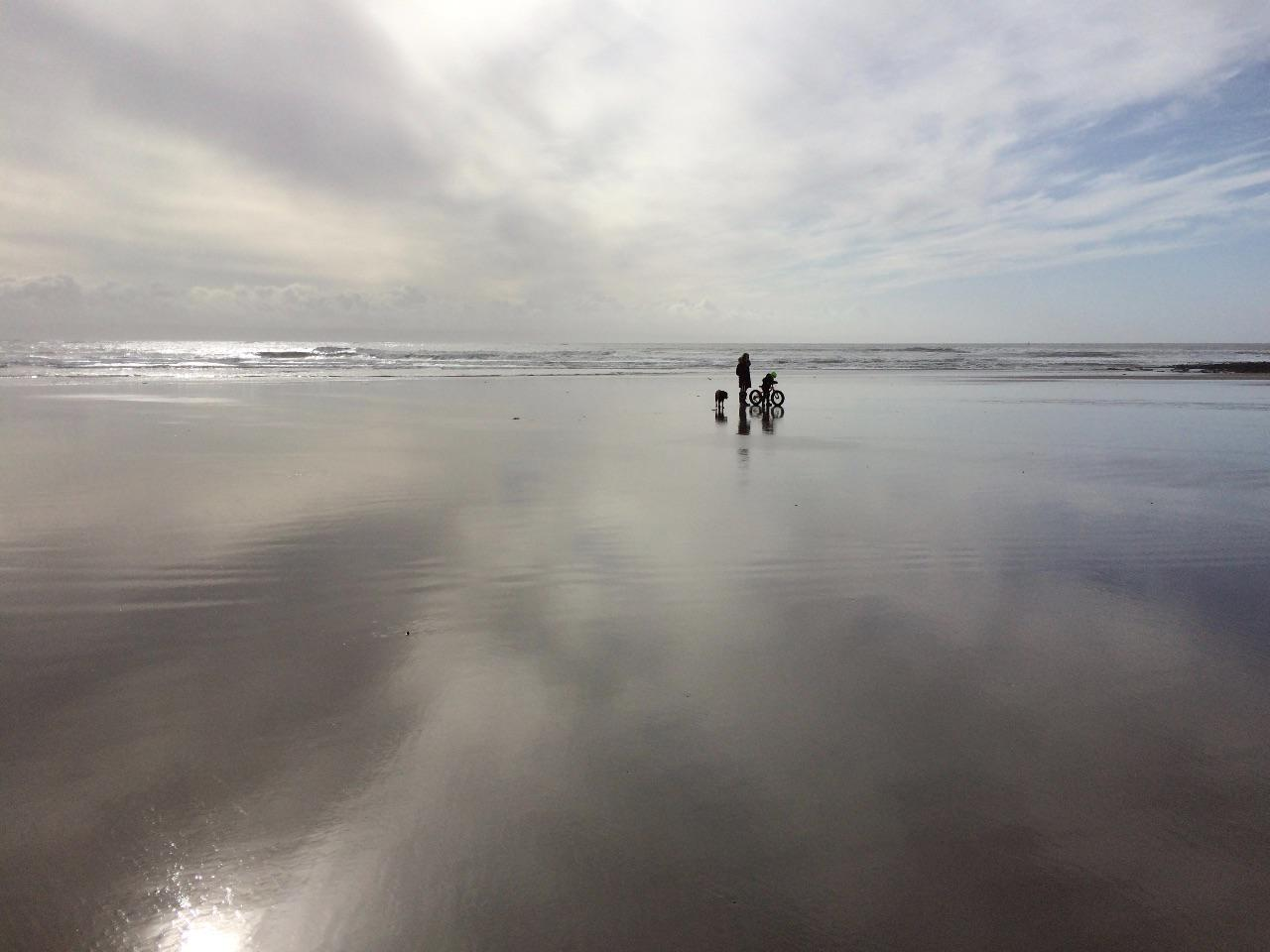 A child on a bike, an adult walking and a dog are silhouetted on the wet sand of Porthcawl at low tide