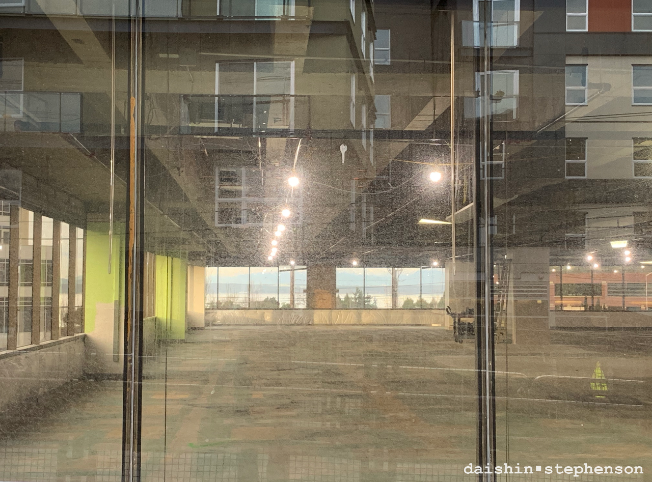 a view through two sets of windows and the reflection of the building behind me
