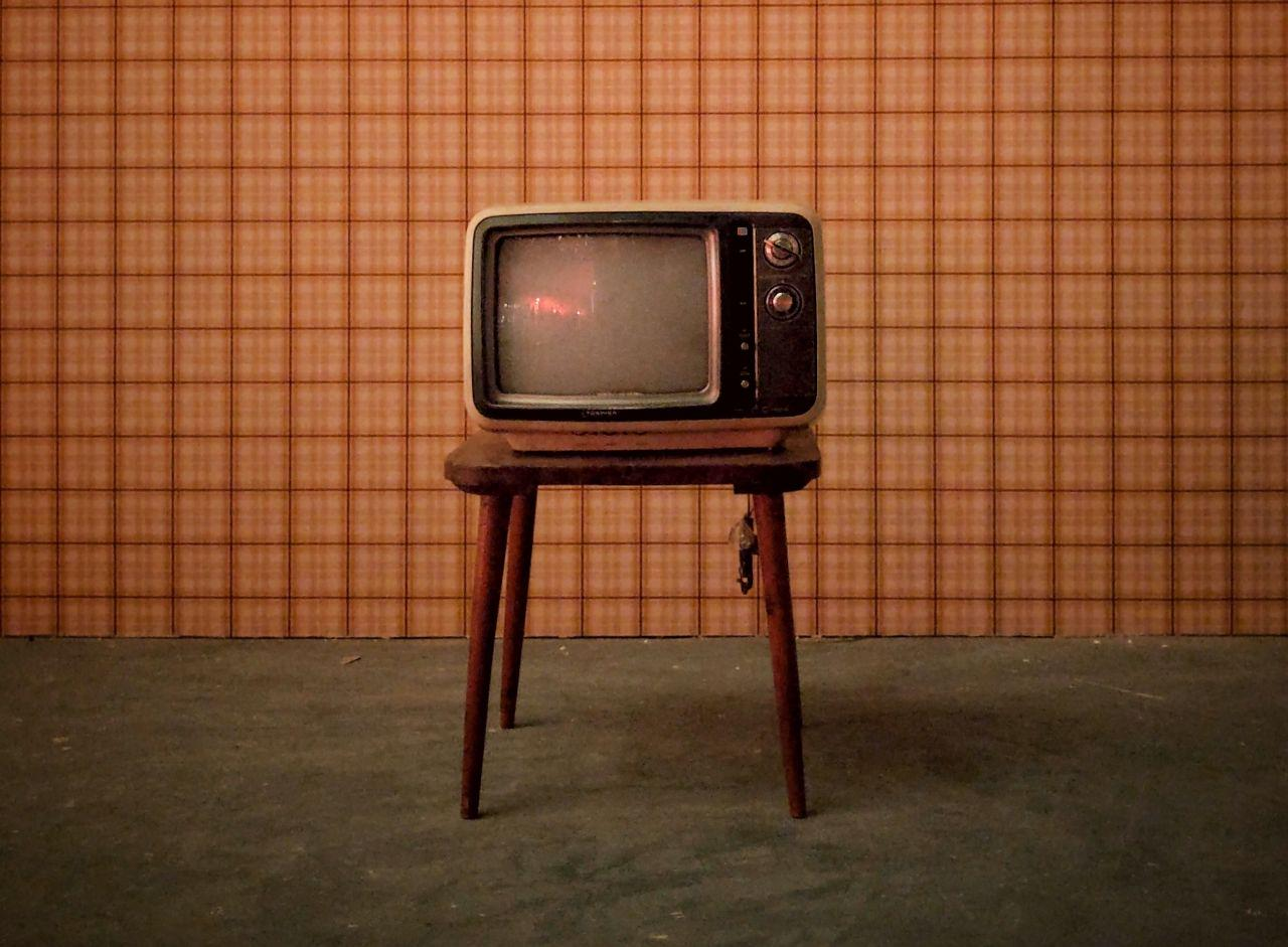 Old TV sitting idly on a small coffee table in the middle of an empty room.