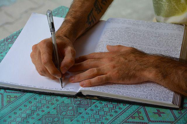 Hands writing in a paper notebook