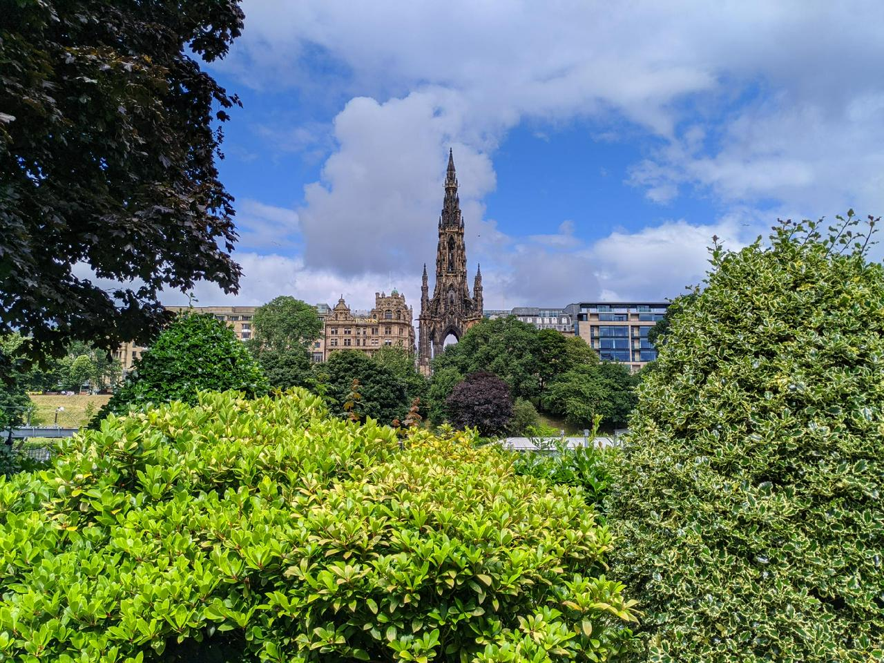 Photo of the Scott Monument. Framed with green, sunlit, foliage.