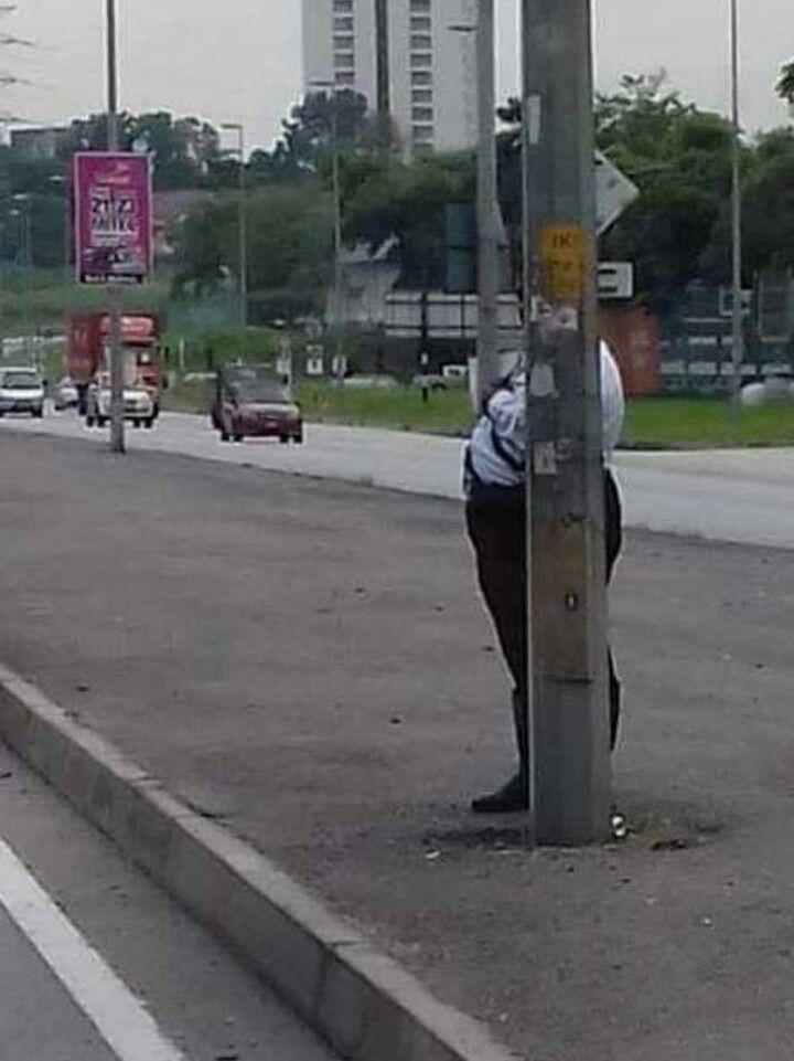 Picture of a traffic policeman attempting to hide behind a lamp post