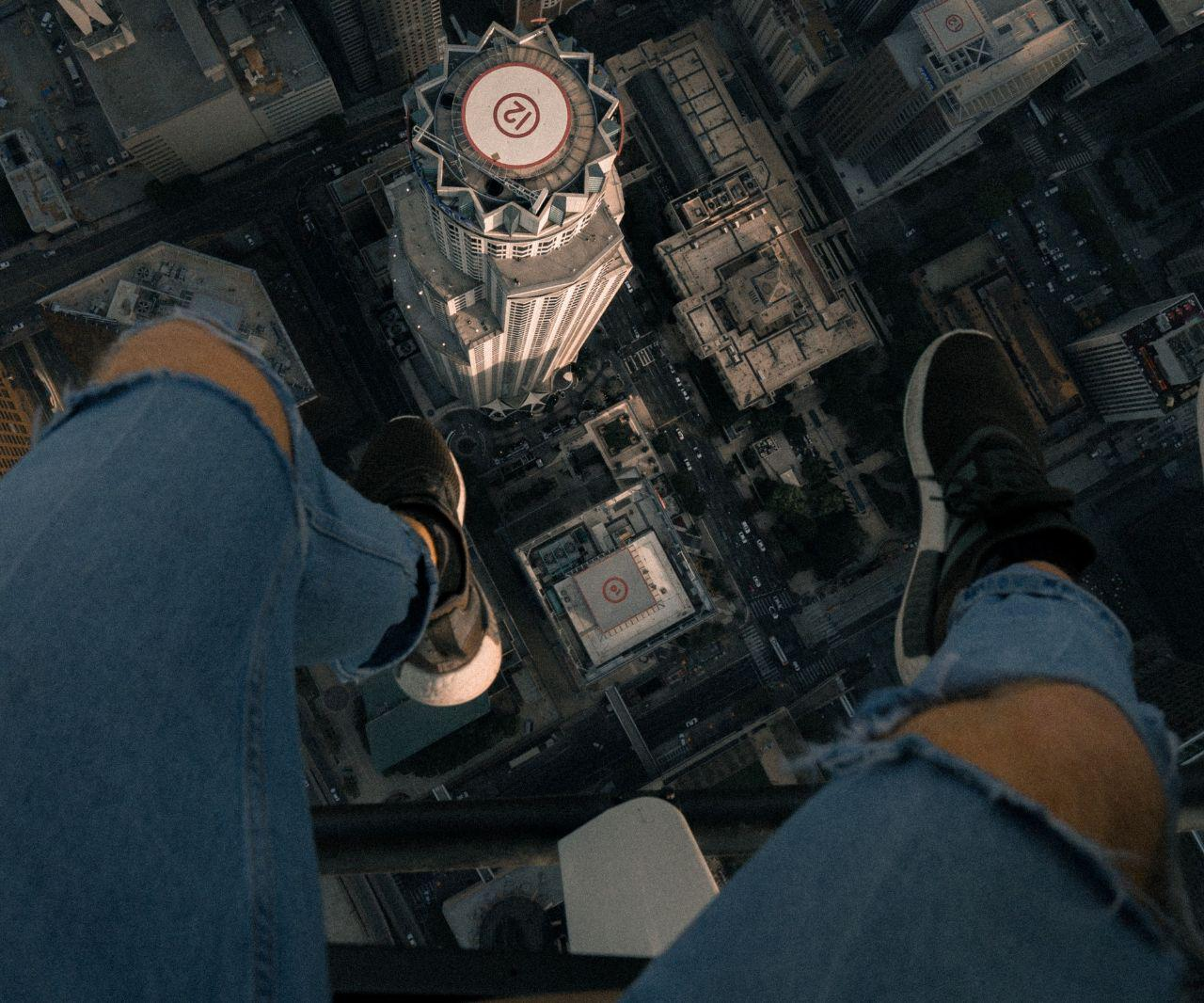 image of legs dangling over edge of building