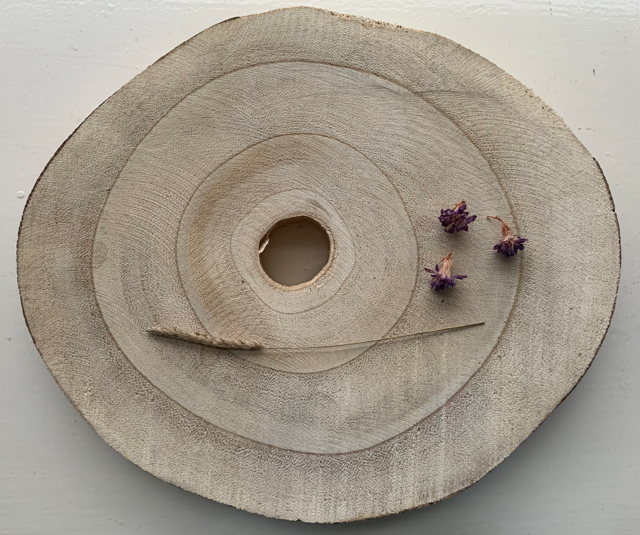 slice of wood showing tree rings with dried flowers and piece of dried grass with a seed head sitting atop it