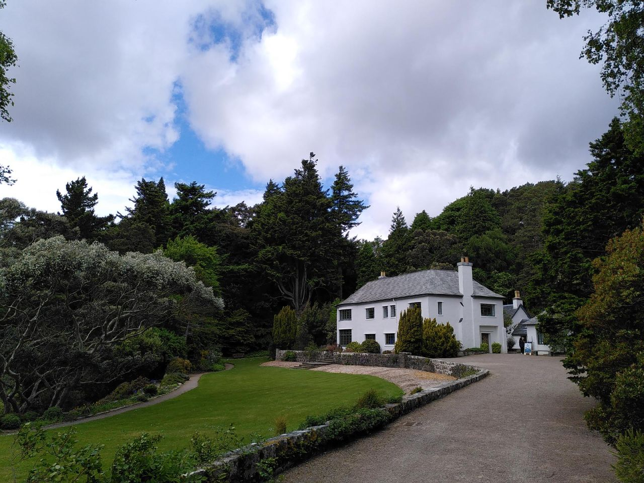 A large, rectangular, white house with steeply slanted slate roof and chimneys book-ending the building. Large green lawn curves across the left of the image and a fine gravel path leads to the house. Tall trees in full leaf surround the building and garden. The sky is overcast.