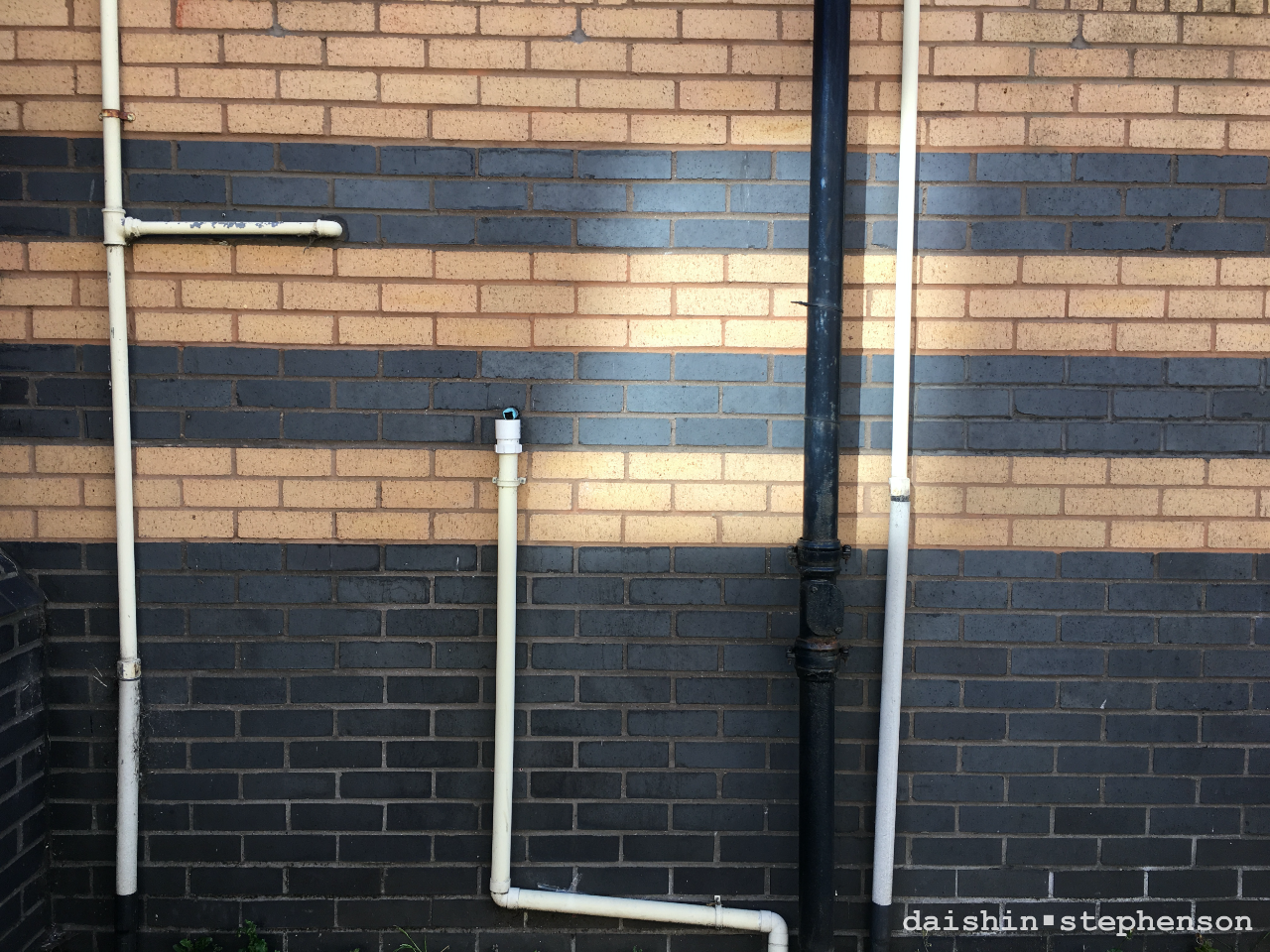 red and black brick wall with white pvc pipes