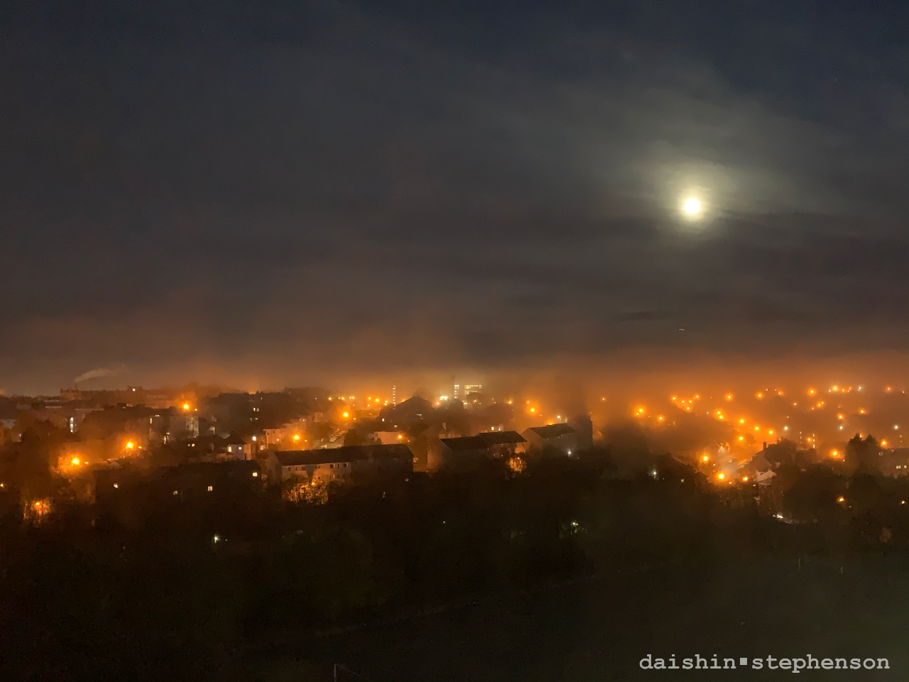 nighttime. fog rolling over neighbourhood illuminated by moon and streetlights