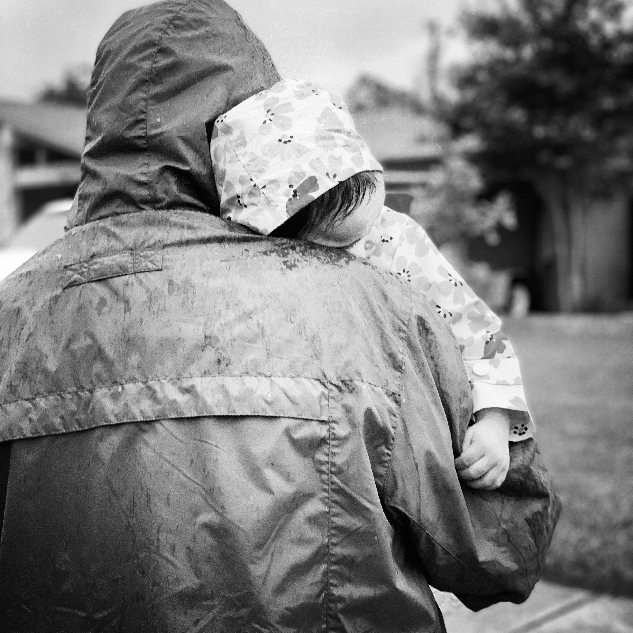 A father holding his toddler daughter in the rain