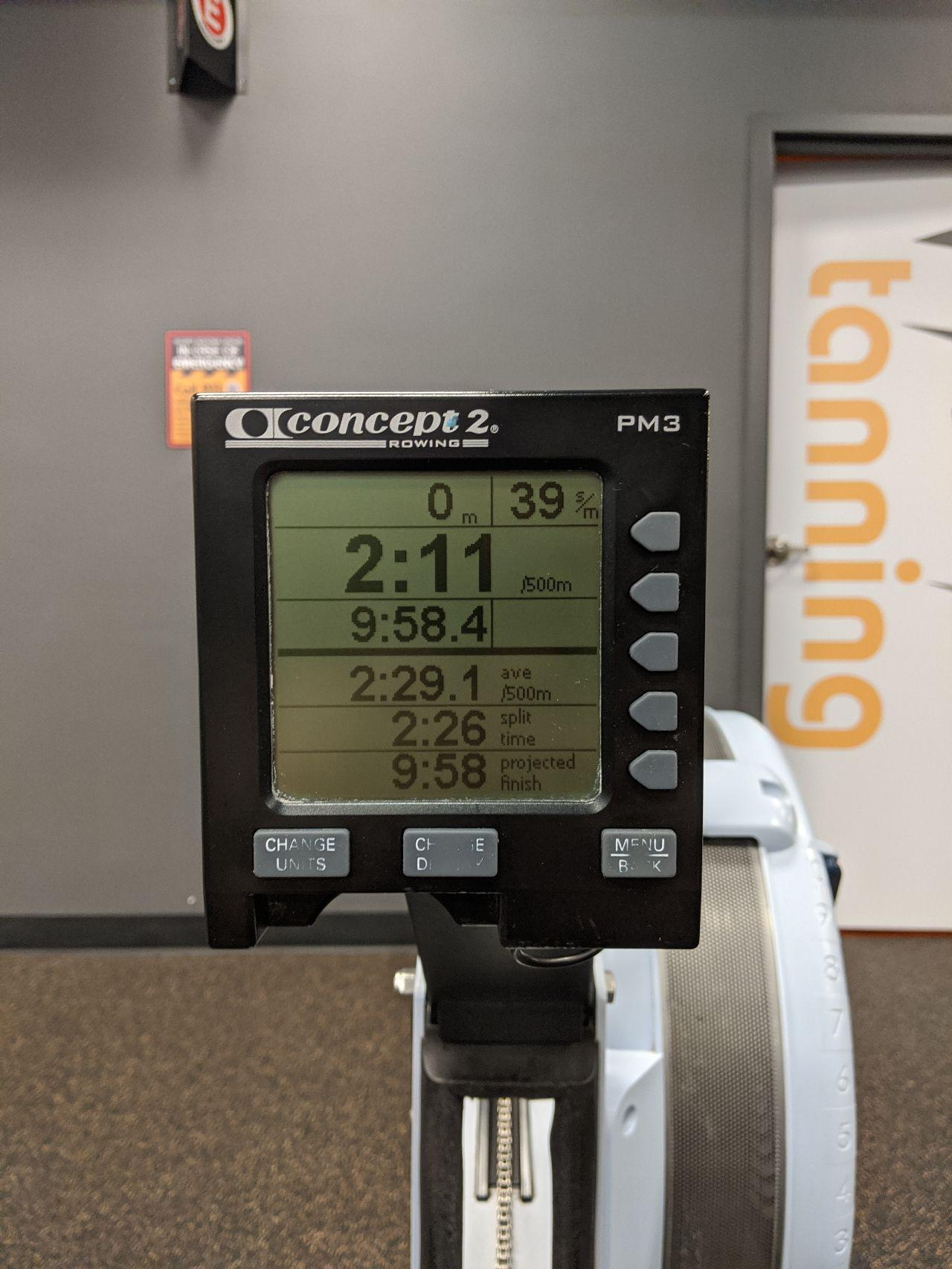 A technical board with a screen attached to a rowing machine. It has various times and numbers on it saying the results of my rowing session.