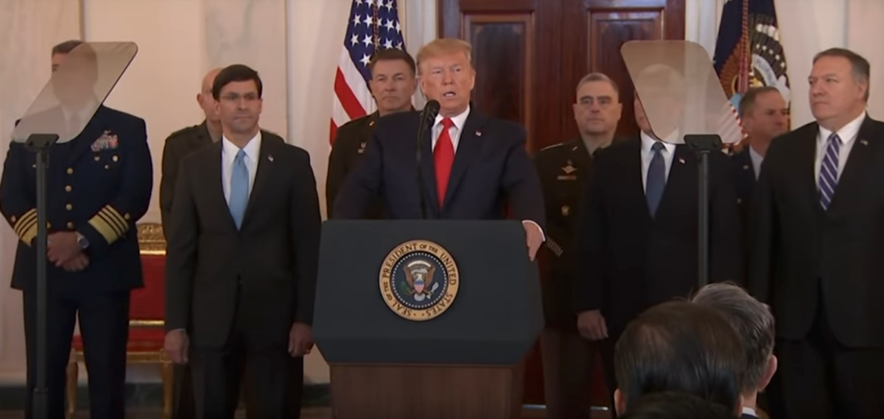 Picture of Trump speaking in front of podium with two pieces of glass suspended on either side of him