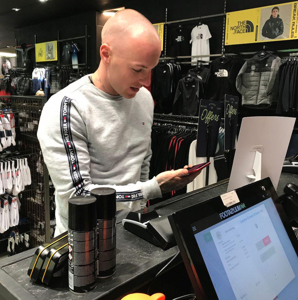 man using contactless payment in store