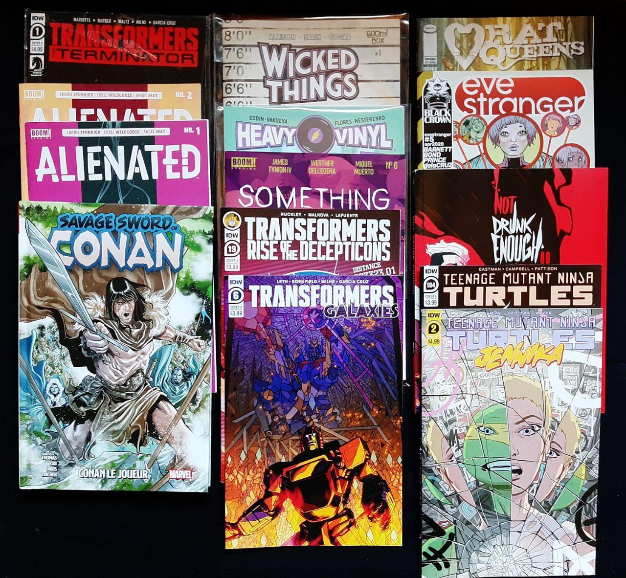 des comics disposés au sol sur un tissu noir