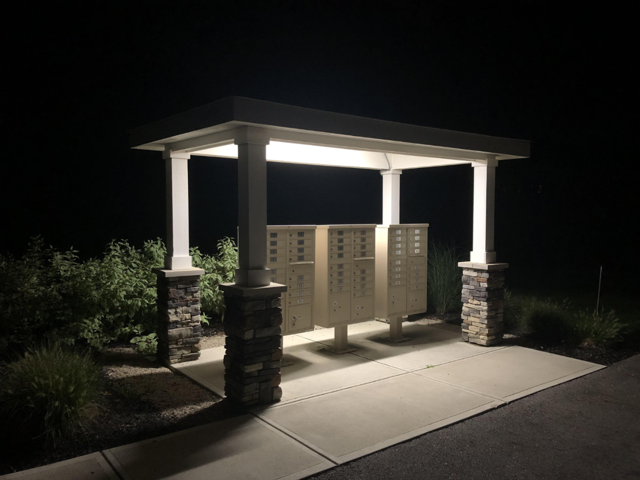 in the dark of the night, a loan set of white postboxes sits underneath a lit up shelter on the path, the back half surrounded by bushes.