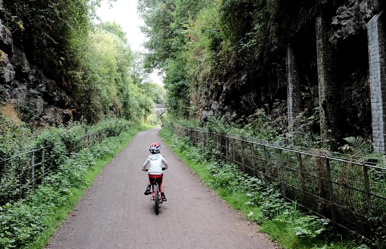 A child rides along a path in a deep cutting on the Monsal Trail